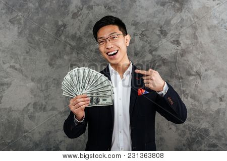 Portrait of a smiling young asian man dressed in suit pointing finger at bunch of money banknotes over gray background