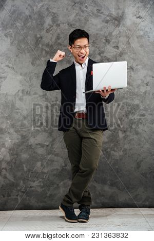 Full length portrait of an excited young asian man dressed in suit using laptop computer and celebrating over gray background