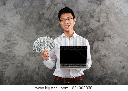 Portrait of a smiling young asian man dressed in shirt showing blank screen laptop computer while holding bunch of money banknotes over gray background