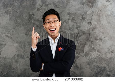 Portrait of a happy young asian man dressed in suit pointing finger up at copy space over gray background