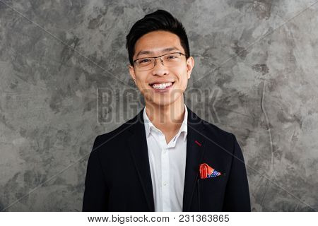Portrait of a smiling asian man dressed in suit looking at camera over gray background