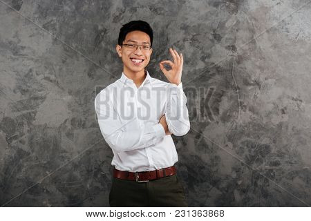 Portrait of a cheerful young asian man dressed in shirt showing ok gesture over gray background