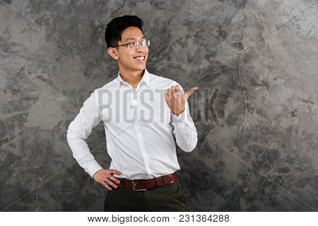 Portrait of a happy young asian man dressed in shirt pointing finger away at copy space over gray background