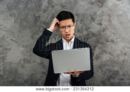 Portrait of a confused young asian man dressed in suit holding laptop computer over gray background