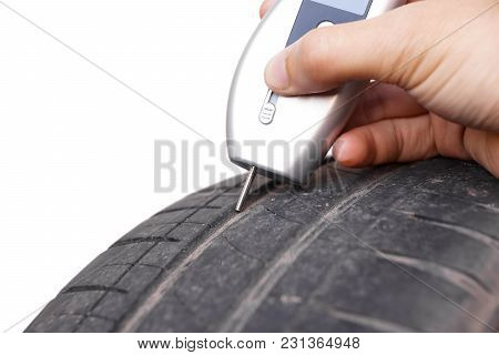 Using A Digital Tire Tread Depth Measuring Tool With Old Tire Isolated On White / Road Safety And Ri