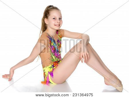 A Girl Gymnast Prepares To Perform The Exercise.the Concept Of Childhood, Sport, A Healthy Lifestyle