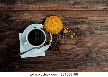 A Cup Of Coffee, Coffee Beans And One Piece Of  Cookies On Wood Background