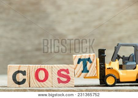 Toy Yellow Forklift Hold Block Letter T To Complete Word Cost On Wood Background