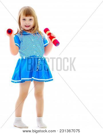 A Cute Little Girl Doing Exercises With Dumbbells. The Concept Of Strength, Health And Sport. Isolat
