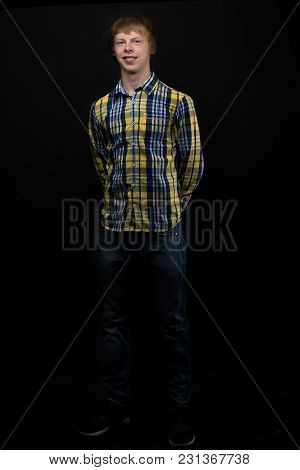 A Young Red-haired Guy Wearing A Shirt And Jeans. On A Black Background.