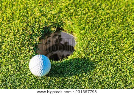 Golf Ball On A Green Lawn. Close-up Photo