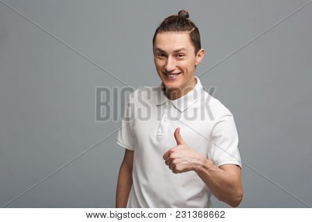Photo of cheerful young man standing isolated over grey wall background. Looking camera showing thumbs up.