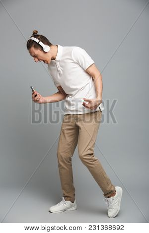 Photo of excited young man isolated over grey wall background listening music in headphones.