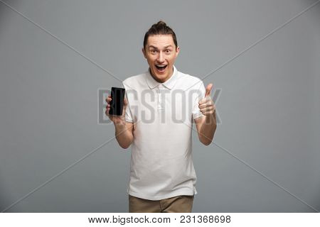 Photo of cheerful young man standing isolated over grey wall background. Looking camera showing display of mobile phone make thumbs up gesture.