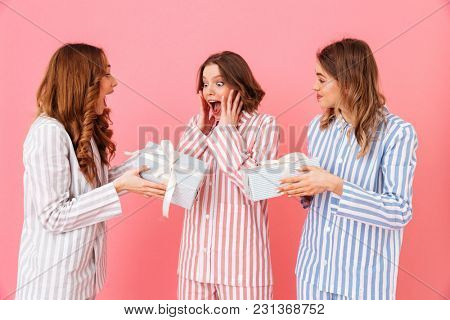 Portrait of three caucasian cute girls 20s wearing colorful striped pajamas rejoicing presents while resting at home isolated over pink background