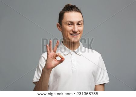 Image of happy young man standing isolated over grey wall background. Looking camera showing okay gesture.