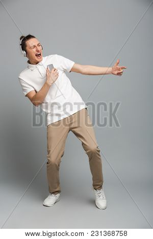 Photo of excited young man isolated over grey wall background listening music in headphones holding mobile phone.