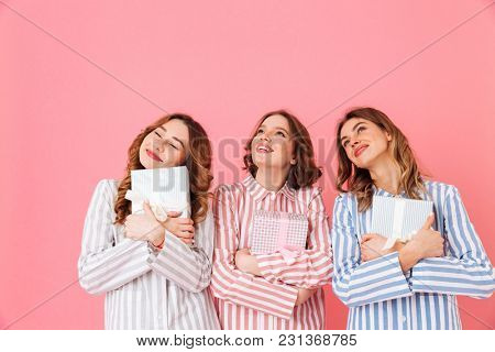 Portrait of three happy girls 20s wearing colorful striped pyjamas looking upward with gift boxes in hands isolated over pink background
