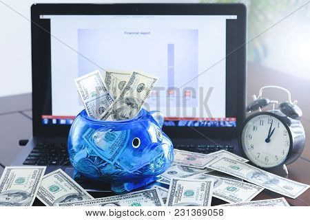 Dollar Money Banknotes In A Piggy Bank And On A Keyboard Of Notebook. American Dollars, Us Banknotes