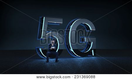 Businessman excited sit on the 3D render 5G futuristic font with blue neon light . Mobile network sp