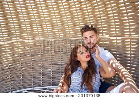 Tourist couple relaxed inside a beach parasol in summer vacation