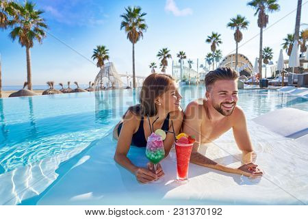 Young tourist couple on infinity pool drinking cocktails at resort on the beach