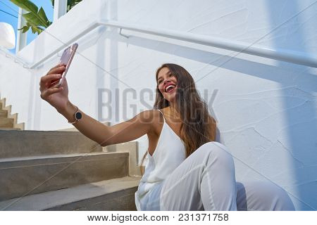 Young latin woman selfie photo smarphone in a white stairway outdoor