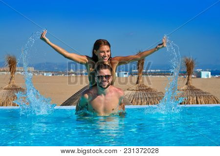 Tourist couple piggyback in infinity pool on a beach resort splashing water