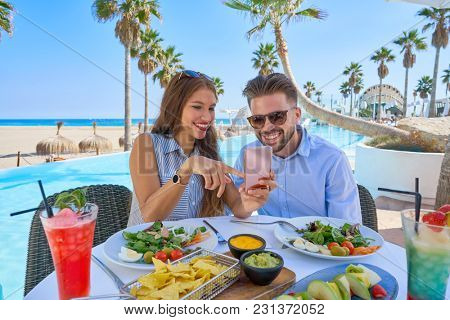 Young couple with smartphone in a swimming pool restaurant