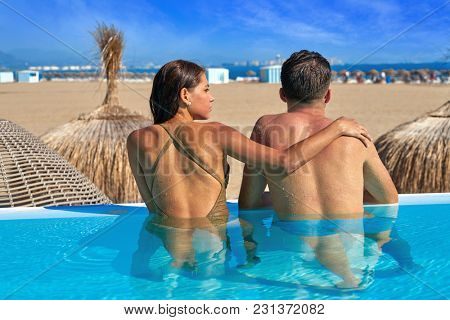 Tourist couple having bath in infinity pool rear back view on a beach resort