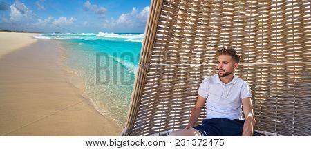 Young beard man in beach parasol at tropical beach in summer vacation photomount
