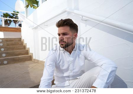 young beard man in a white starway outdoor