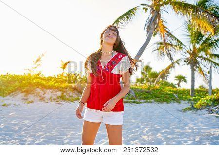 Happy latin beautiful girl in caribbean palm trees sunset beach