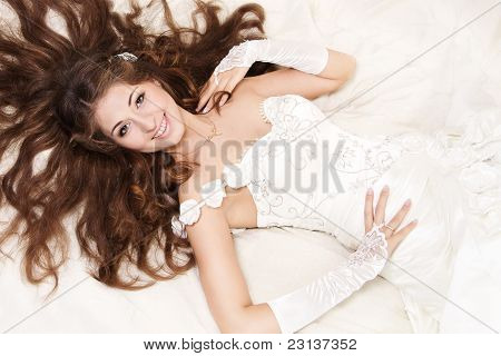 Smiling Bride With Curly Long Hair Lying Over White. High Angle View.