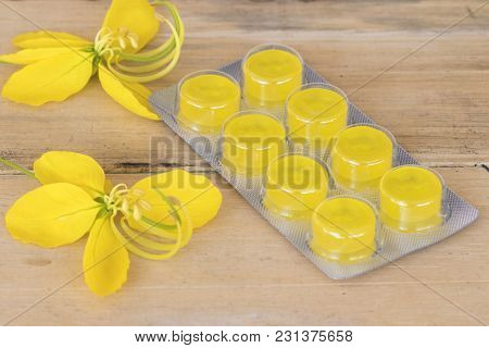 Cough Sore Throat Pastille With Yellow Flowers On Background Wooden
