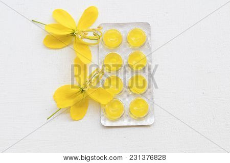 Cough Sore Throat Pastille With Yellow Flowers On Background White