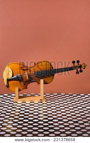 Violin On A Wooden Stand On A Brown Background