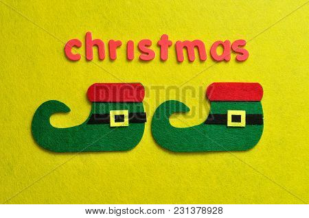 An Elf's Shoes Displayed With The Word Christmas On A Yellow Background