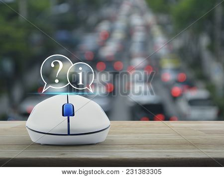 Question Mark And Information Chat Icon With Wireless Computer Mouse On Wooden Table Over Blur Of Ru