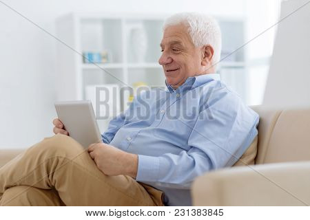 Smiling Senior Man Sitting In Comfy Armchair And Watching Videos On Digital Tablet