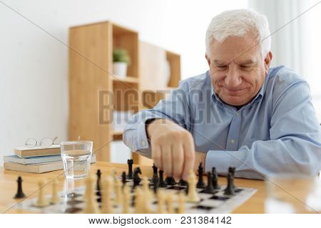 Senior Smiling Man Enjoying Playing Chess In Nursing House