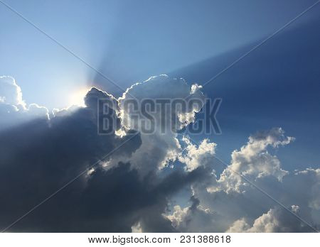 White fluffy clouds and sun reflect, in the blue sky, the cumulus occur in the bright morning. For background or display or backdrop poster