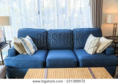 Fabric Pillows On A Blue Sofa And A Wicker Table With Modern Lamp In Livingroom With Light From Wind