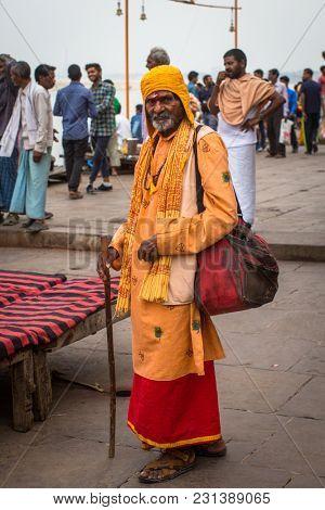 VARANASI, INDIA - MAR 15, 2018: Sadhu (holy man) on the Dashashwamedh Ghat of Ganga river. Varanasi is most important pilgrimage sites in India, one of the 7 sacred cities of Hinduism.