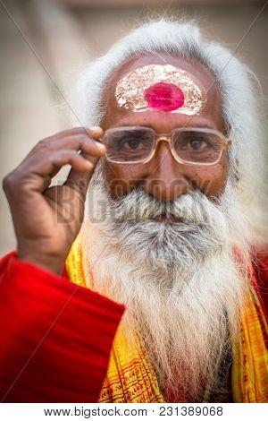 VARANASI, INDIA - MAR 15, 2018: Sadhu (holy man) on Dashashwamedh Ghat is the main and probably oldest ghat of Varanasi located on the Ganges, close to Kashi Vishwanath Temple.