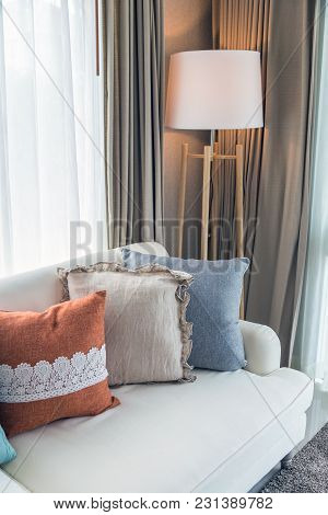 An Vertical Interior Picture Of Livingroom With Colorful Pillows On Beige Sofa And Modern Lamp On Gr