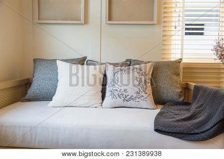 Beautiful Pillows And Yarn Blanket On Beige Fabric Sofa With A Frames On A Beige Wall In Livingroom