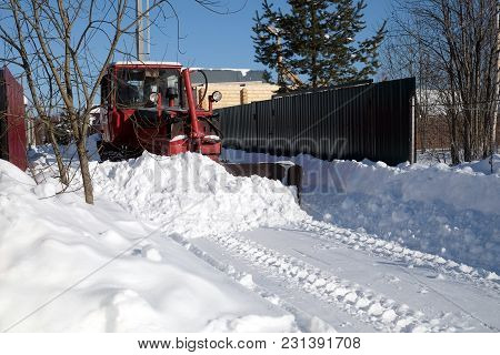 Diesel Caterpillar Tractor Cleans The Road From Snow In A Country Village On A Bright Sunny Day Side