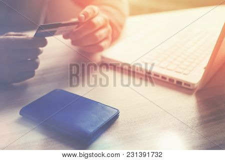 Man Holding Bank Card. Laptop And Wallet On The Table. Internet Shopping, Intentional Sun Glare And