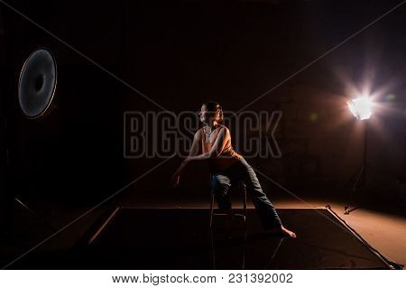Woman In A Yellow T-shirt In A Dark Studio Illuminated By Colored Spotlights During Photoshoot
